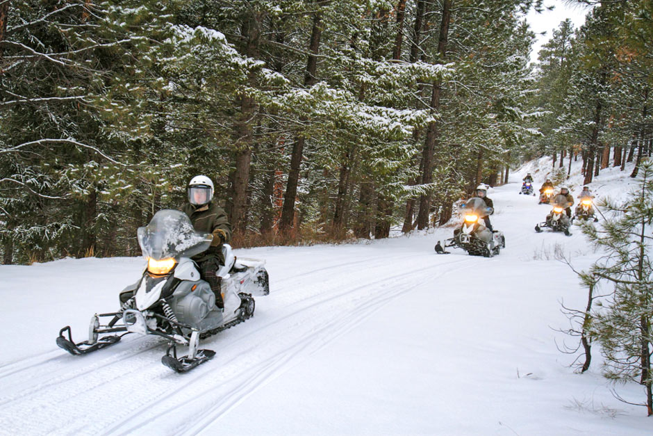 group snowmobiling on a trail
