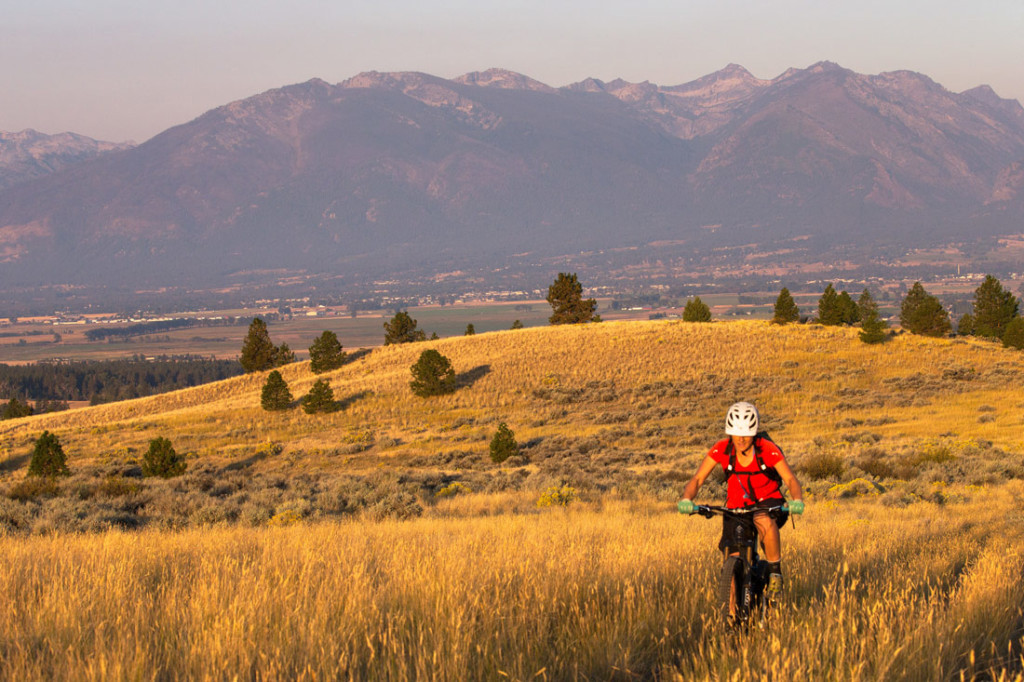 woman mountain biking with Montana's bitterroot mountains in background