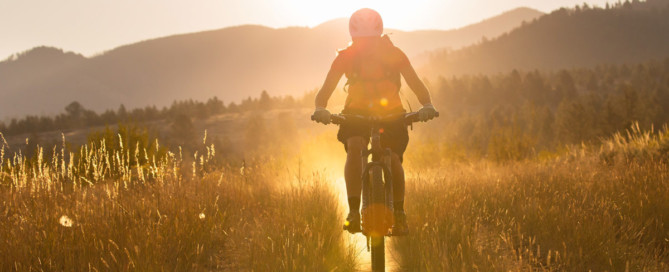 woman mountain biking in morning sun in bitterroot valley montana