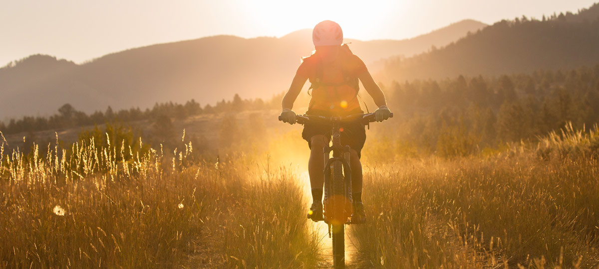 woman mountain biking in morning sun in bitterroot valley montana