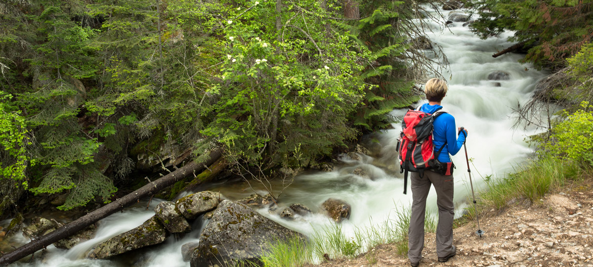 woman hiking with water cascading