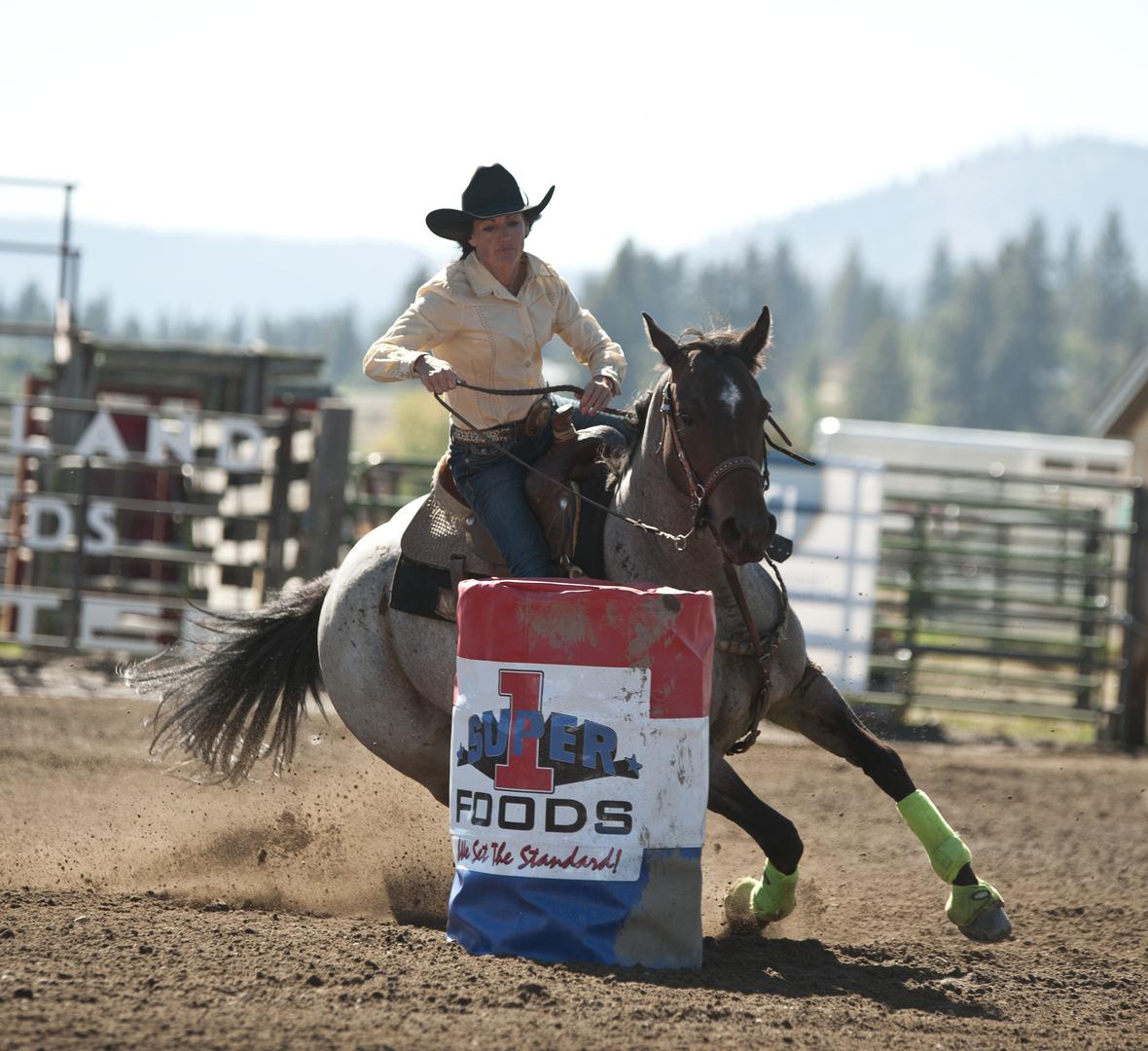 rodeo rider and horse running around barrel