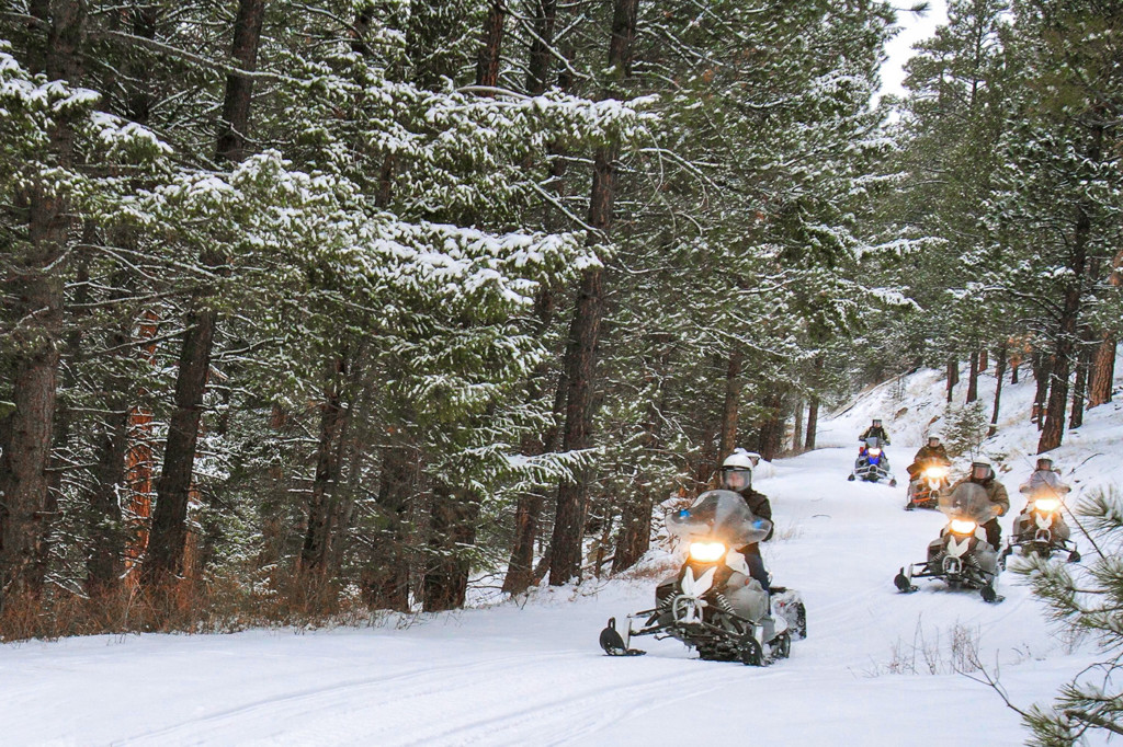 group snowmobiling on groomed trails in Bitterroot mountain range