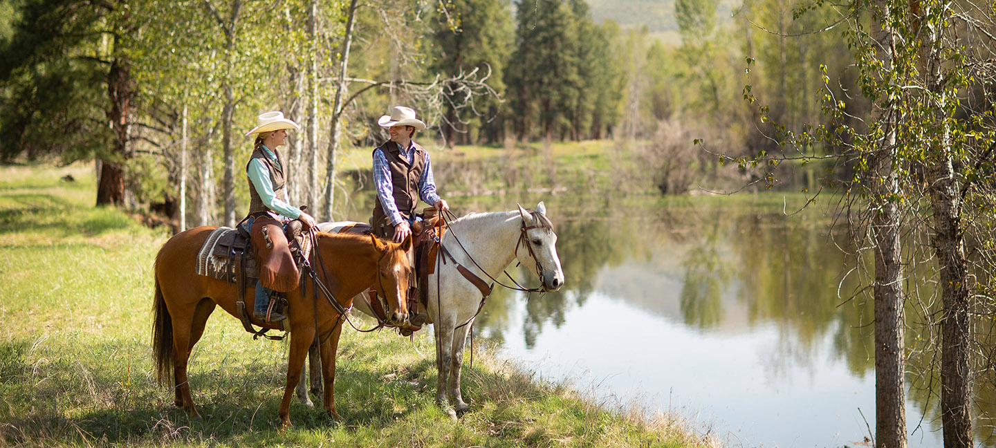 two horseback riders at pond on montana vacation